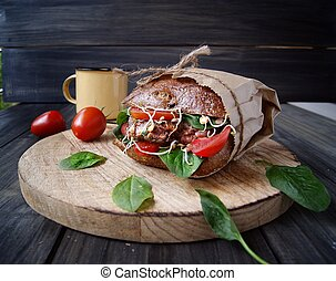 hamburger with black bread and tomatoes on table - hamburger...