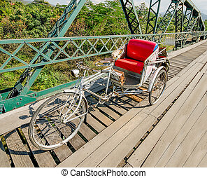Tricycle bicycle on old  bridge in the north of thailand