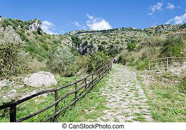 sentiero di montagna con staccionata in legno e cielo...