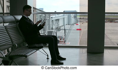Businessman in Airport Waiting Room - Man looking through...