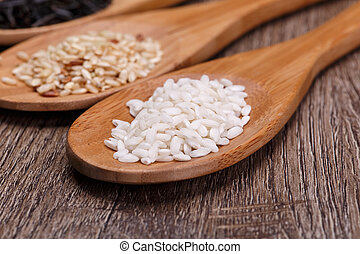 White, wild and brown rice in a wooden spoons