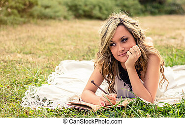 Romantic girl writing in a diary lying down outdoors -...
