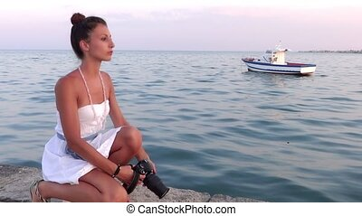nice girl taking a photograph - Young photographer. Blue sea...