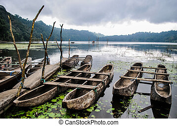 Boats at Lake Tamblingan, murky atmosphere of Bali.