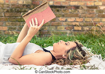 Romantic girl reading a book lying outdoors - Portrait of...