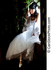 Bride - Pretty bride is sitting on the windowsill. Portrait...