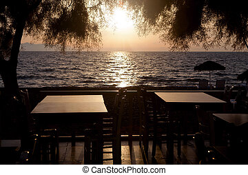 Sunset on the sea, the view through the tables of the...