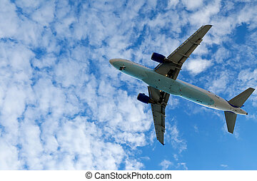 Airplane in the bright sky - Jet airplane landing in bright...