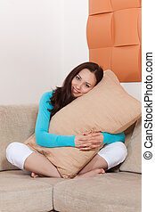Young woman sitting on a sofa with a pillow