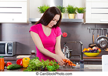 Young woman washes the vegetables in  domestic kitchen