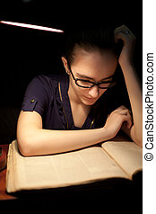 Girl reading book in dark library