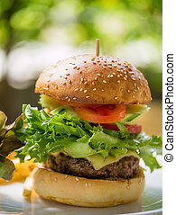 Classic deluxe cheeseburger with lettuce, onions, tomato and...