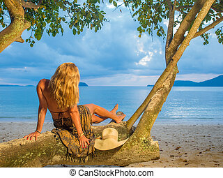 Woman relaxing on the beach in Thailand at sunset