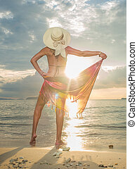 Woman with sarong on the beach at sunset in Thailand