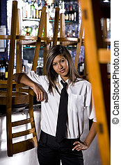 Hispanic bartender in closed bar - Young female Hispanic...
