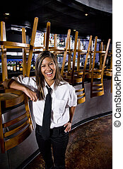 Bartender in closed bar - Hispanic worker standing next to...