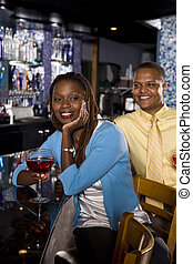 Couple at a bar - Young African couple sitting at a bar