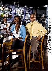 Couple at a bar - Couple sitting at the bar of a restaurant
