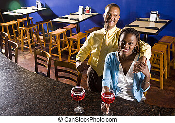 Couple having drinks in a restaurant - Young African couple...