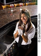 Happy bartender - Hispanic female bartender drying hands...