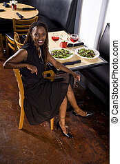Woman dining in restaurant - Attractive African woman in a...