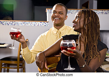 Couple having drinks in restaurant - Young African American...