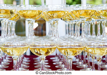 Heap of glasses filled with champagne on a table