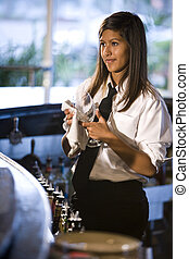 Bartender cleaning a wine glass - Young Hispanic female...