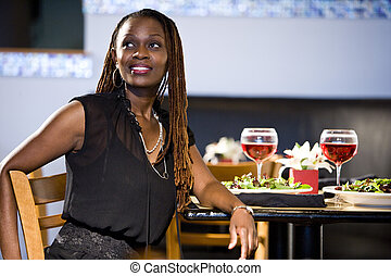 Woman eating in restaurant - Attractive African woman...
