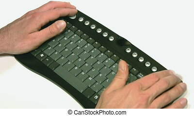 Hands working on small black keyboard on white - Hands using...