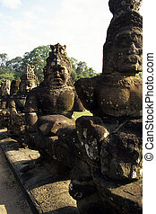 Deva and asura statues holding nagas in a tug-of-war outside...