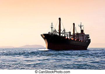 Silhouette of cargo ship - Cargo ship sailing into Sea on...