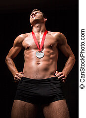 Muscular man with medal on his chest - studio shoot