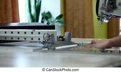 Worker configures and starts sewing machine
