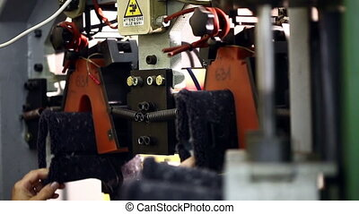 View of worker fixes boots in machine, close-up