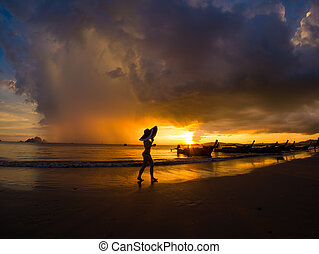 Woman on the beach at sunset on Ao Nanag beach in Krabi...