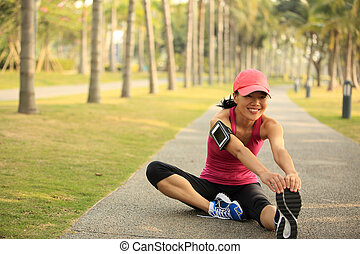 woman runner stretching legs - woman runner stretching legs...