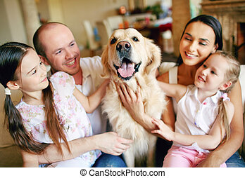 Cuddling dog - Cute girls and their parents cuddling dog
