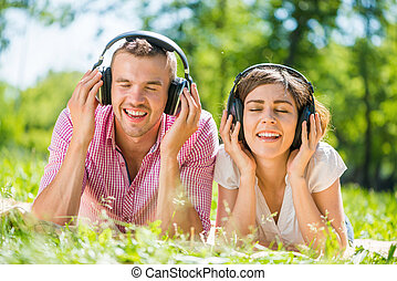 Couple in park - Young couple in summer park listening music