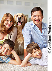 Parents, kids and pet - Happy young couple, their sons and...