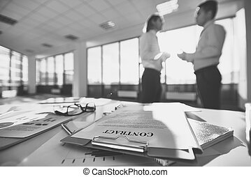 Business documents - Business papers on the desk and two men...