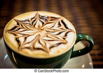 Cup of coffee latte with design art in froth, on a wooden...
