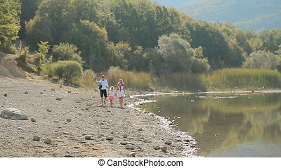 Happy family with two young daughters walking along the lake