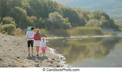 United family with two young children walking along the lake view from the back
