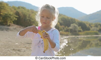 Portrait of little blond girl who eats banana while standing...