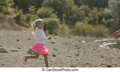 Little blond girl running toward father and he whirls her in...