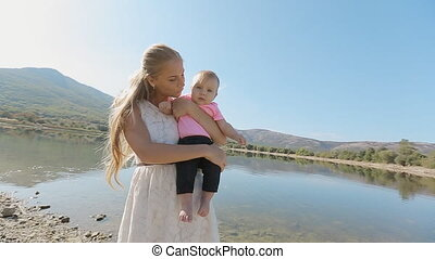 Young mother holds on hands charming baby daughter on background of beautiful mountain landscape