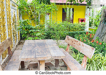 the old wooden table and chair in the garden near the tree