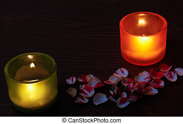 Glass candlesticks, rose and rose petals on wooden table