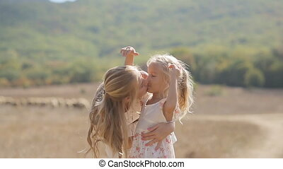 Young beautiful mother kissing little daughter and circling her in slow motion